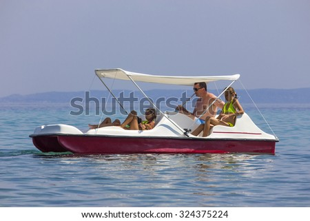 Family on the pedal boat - stock photo