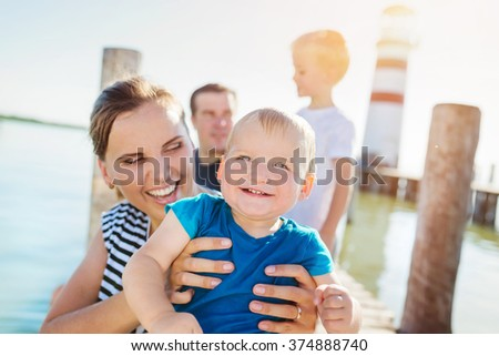 Family on the pier at the lighthouse, sunny summer day - stock photo