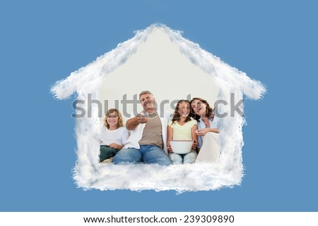 Family on the sofa watching tv against blue background with vignette - stock photo