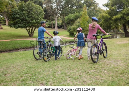 Family on their bike at the park on a sunny day - stock photo