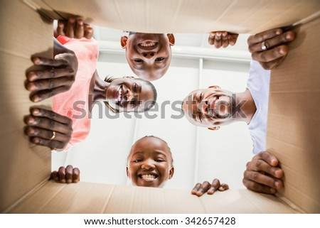 Family opening box in new home in living room - stock photo