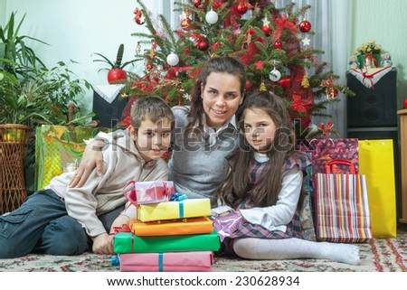 Family Opening Christmas Gifts At Home In Front Of Christmas Tree - stock photo