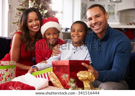 Family Opening Christmas Presents At Home Together - stock photo