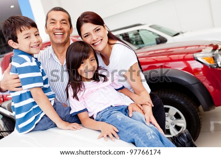 Family out shopping for a new car at the dealership - stock photo