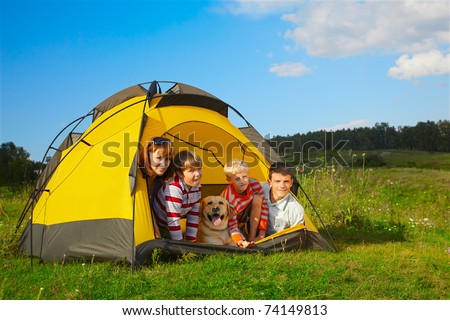 family outdoor portrait of smiling mother, two boys, young man and labrador looking happy outside of tent - stock photo