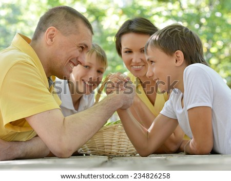 Family outdoors at table,father and son doing arm wrestling fight - stock photo
