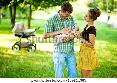 family outdoors in park, soft focus (focus on eyes of baby and mother)
