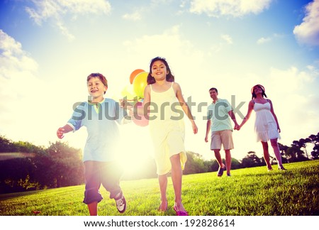 Family outdoors walking toward the camera. - stock photo