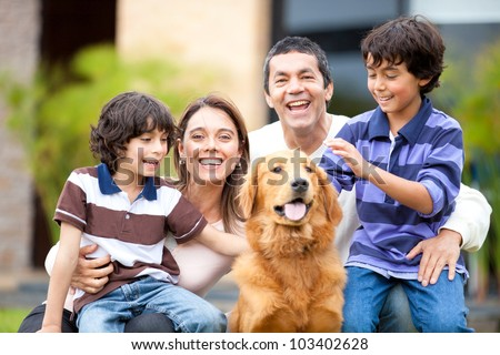 Family outdoors with a dog looking very happy - stock photo