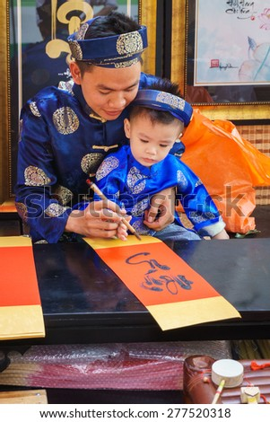 Family painter artist/HoChiMinh, Vietnam   February 9th 2015: This artist and his son were painting the image in his shop, in HoChiMinh, Vietnam  - stock photo