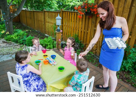 Family painting and decorating Easter eggs together outside in a garden setting during the springtime. Mother hands out eggs to her happy children to dye their eggs.   Part of a series.  - stock photo