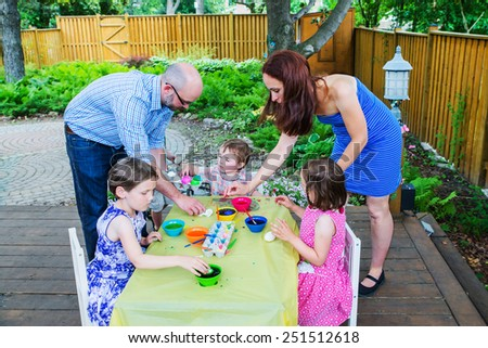 Family painting and decorating eggs.  Mother and father help their children color dye their Easter eggs outside during the spring season in a beautiful garden setting. Part of a series.    - stock photo
