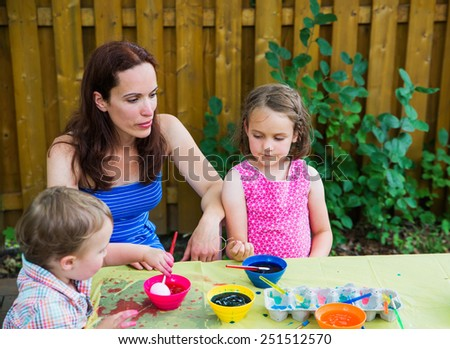 Family painting and decorating eggs.  Mother looks on at her children having fun as they color dye their Easter eggs outside during the spring season in a garden setting.  Part of a series.  - stock photo