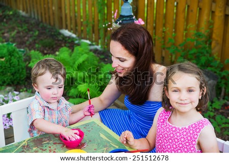 Family painting and decorating eggs outside during spring season in a garden setting.  Mother smiles at her boy color dying an Easter egg pink   A girl  in the foreground smiles.  Part of a series.   - stock photo