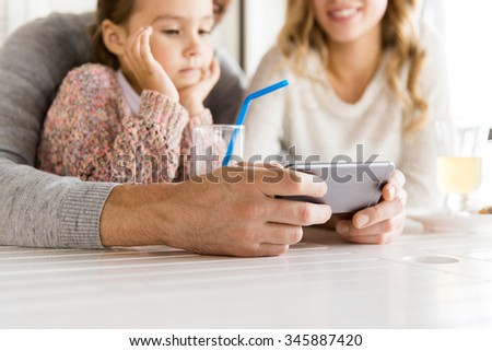 family, parenthood, technology and people concept - close up of mother, father and little girl with smartphone having dinner at restaurant - stock photo