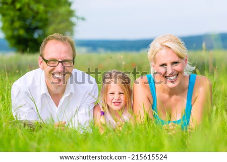 Family, Parents and daughter laying on grass of lawn or field