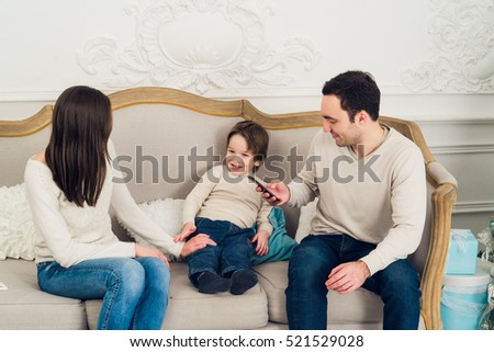 family phone talking - cute little boy, his mother and father are sitting on the sofa