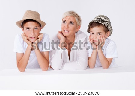 Family photo. Beautiful blonde mother posing with two young boys, looking at camera.