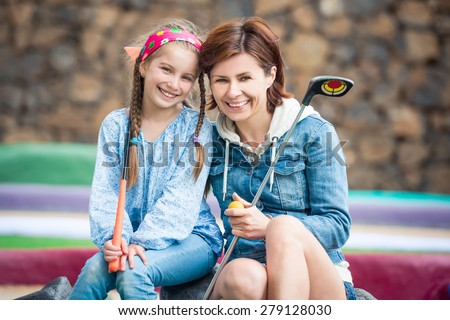 Family photo. Happy Mother and daughter on the golf course - stock photo