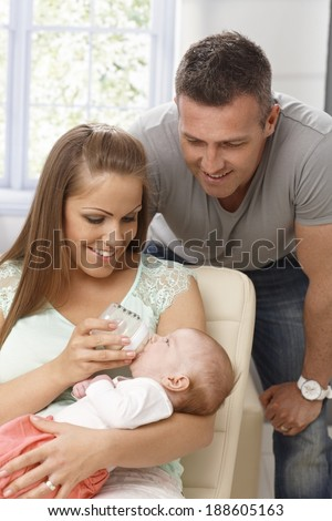 Family photo of young mother feeding newborn baby, father looking them with pride.