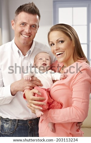 Family photo with newborn baby, parents smiling happy, looking at camera. - stock photo