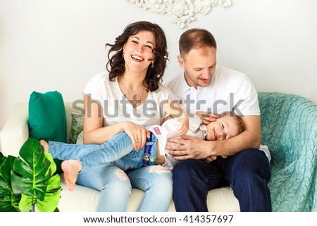 Family photo. Young couple: mother, father and baby sitting on the couch at home. They hug and laugh. Bright, spring, warm picture.