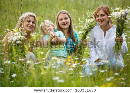 Family picking summer flowers in meadow - stock photo