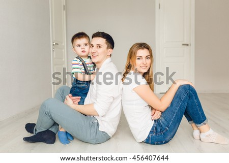 Family picture of two young parents playing with their boy child. They sit on the floor and father holds his son. They wear white t-shirt and jeans. - stock photo