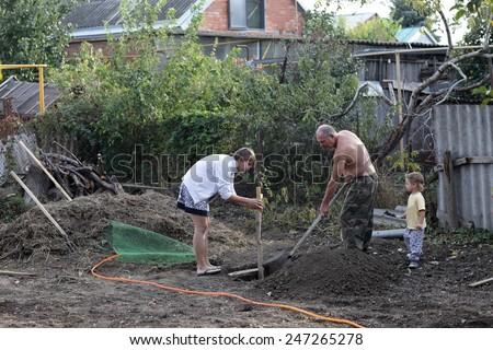 Family planting seedlings of fruit trees in ground - stock photo