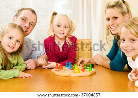 Family playing a board game together having a lot of fun