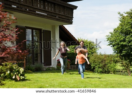 Family playing a game of tag chasing each other in front of their new home - a single house