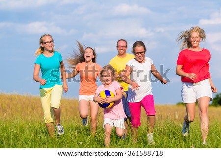 Family playing ball games on meadow running and having fun - stock photo