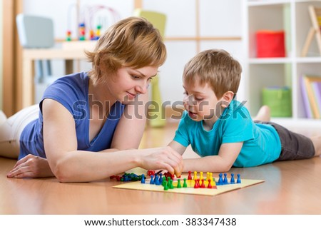 Family playing board game at home on the floor at home - stock photo