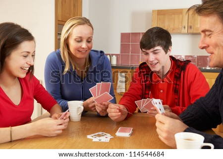Family Playing Cards In Kitchen - stock photo