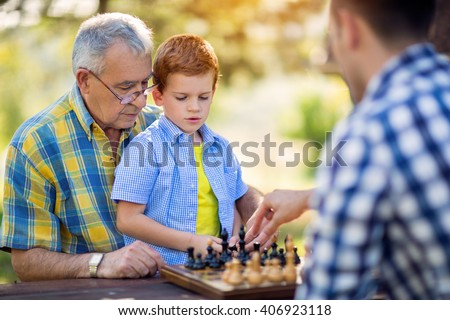 family playing chess in the nature - stock photo