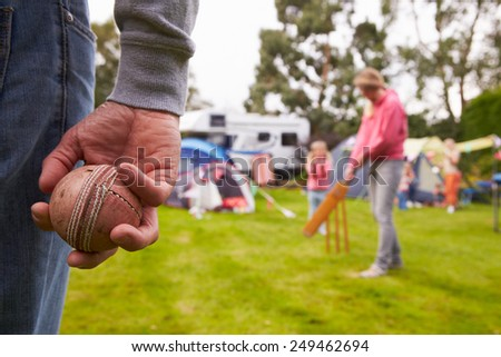 Family Playing Cricket Match On Camping Holiday   - stock photo