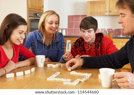 Family Playing Dominoes In Kitchen - stock photo