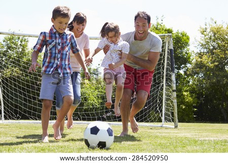Family Playing Football In Garden Together - stock photo