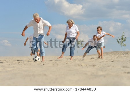 Family playing football on a beach in summer day - stock photo