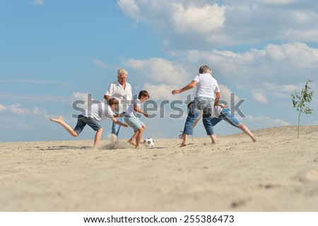 Family playing football on a beach in summer day