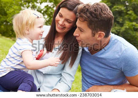 Family Playing Game In Garden With Daughter - stock photo