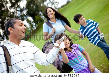 Family playing golf and walking to the next hole - stock photo