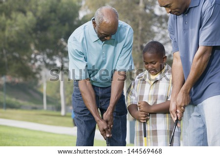 Family playing golf together - stock photo