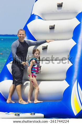 Family Playing on an Inflatable toy at the beach - stock photo