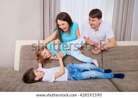 Family playing on sofa at home.