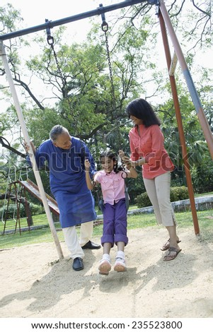 Family Playing on Swing - stock photo