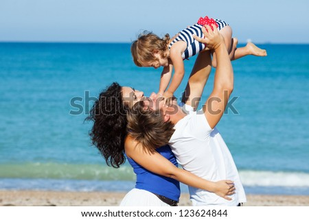 Family playing on the beach - stock photo
