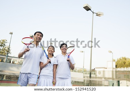 Family playing tennis, portrait - stock photo