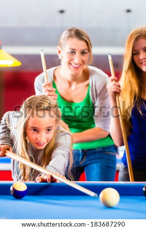 Family playing together billiard. Brother kick off with queue and balls on pool table  - stock photo
