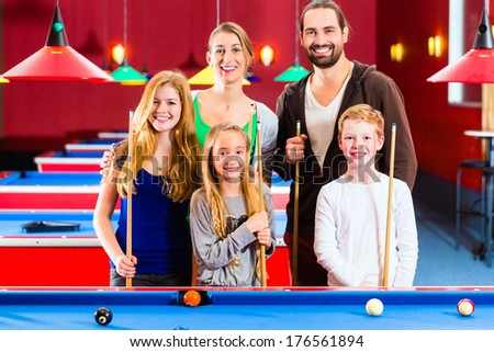 Family playing together billiard with queue and balls on pool table  - stock photo